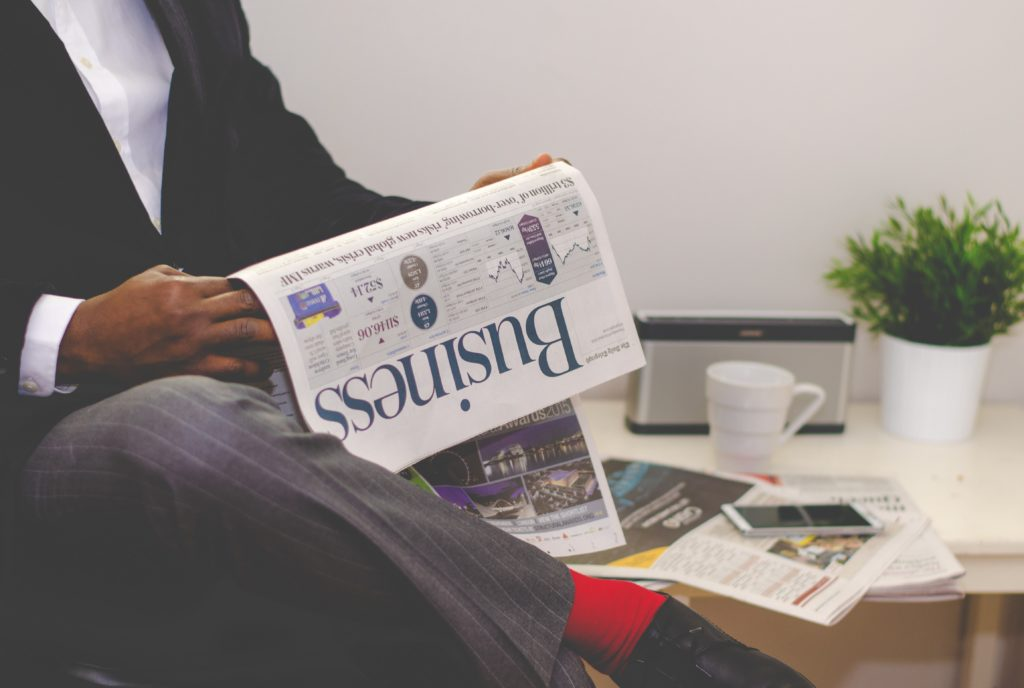 Man in suit reading business section of newspaper