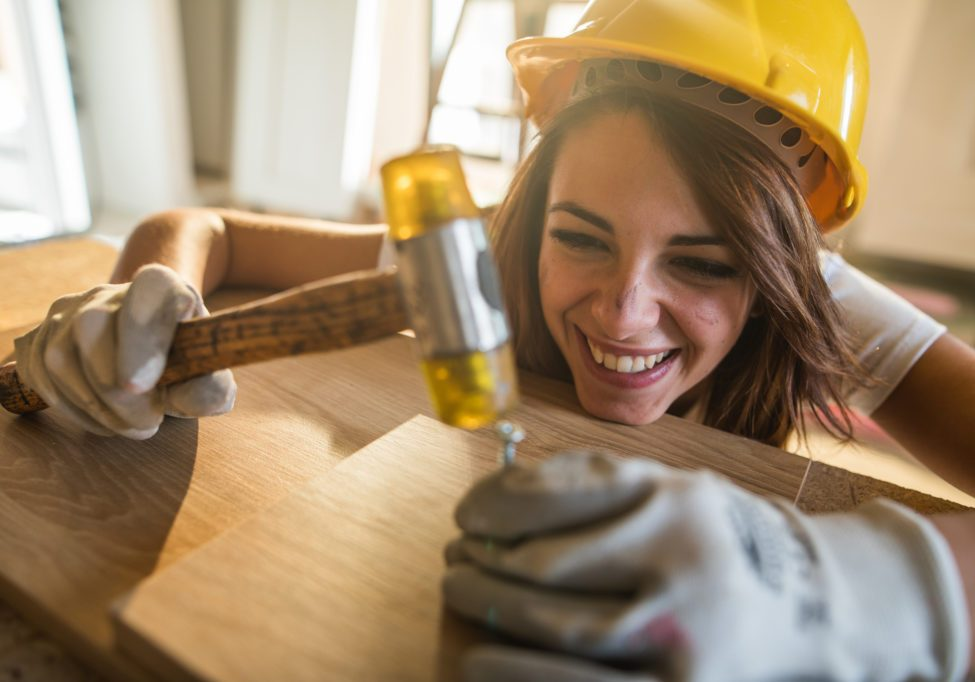Happy female worker hammering the nail into the plank.