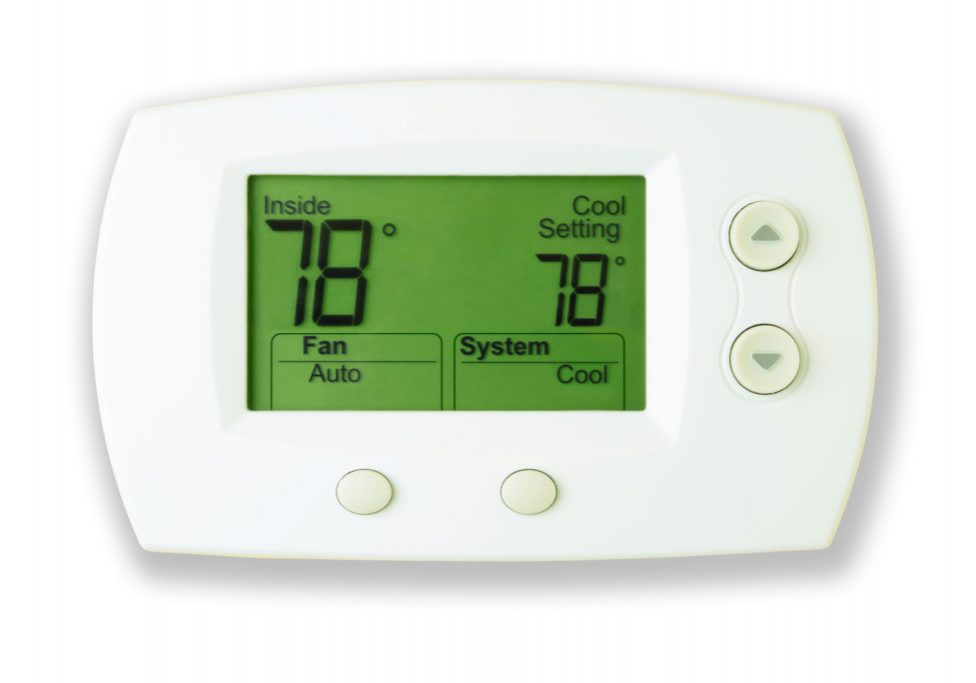 A white digital thermostat with lit display