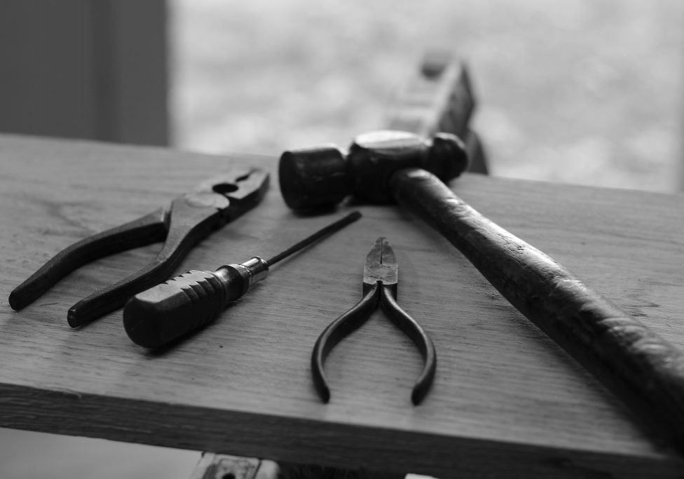 Hand tools including pliers, hammer, screwdriver