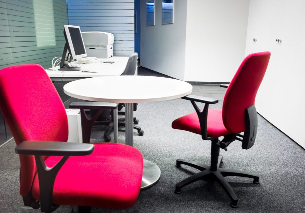 Red office chairs, desk, computer, printer, another office supplies