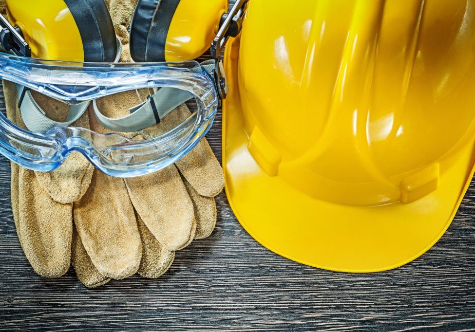 Safety gloves, goggles, earmuffs, and hard hat on wooden board