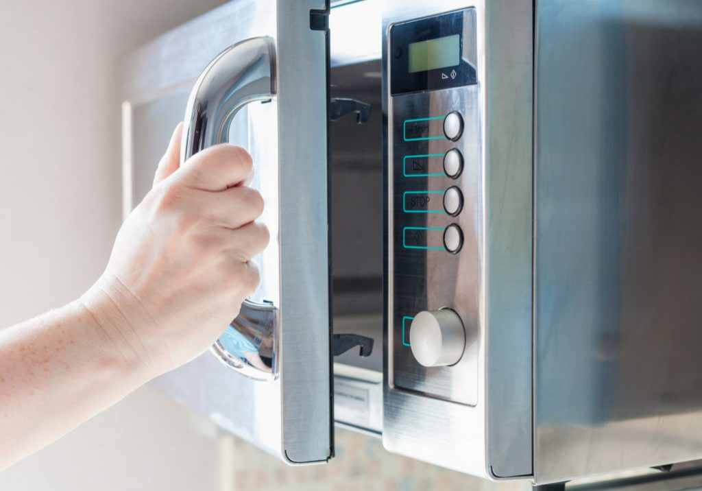 Hand opening microwave oven to cooking food