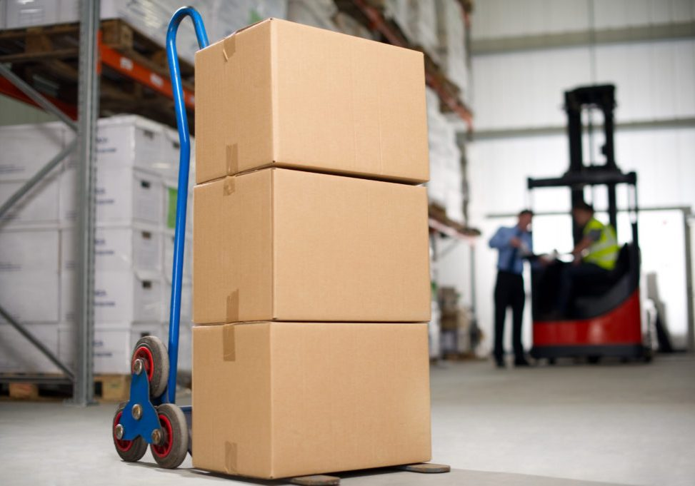 Stack of cardboard boxes sit on a hand truck as two warehouse employees work in the background.