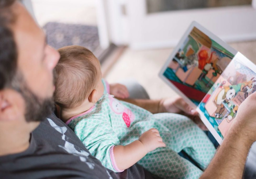 Father reading a children's book to his baby