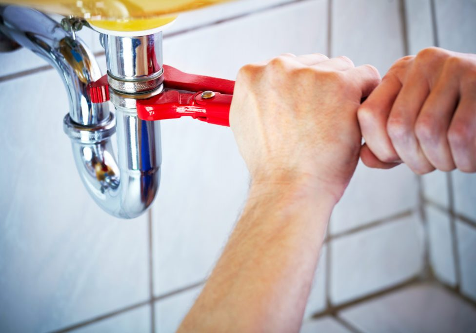 Plumber holding wrench and fixing a sink in bathroom